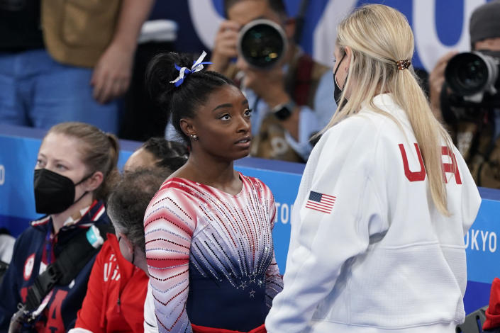 Simone Biles, of the United States, speaks with her coach Cecile Landi after performing on the balance beam during the artistic gymnastics women's apparatus final at the 2020 Summer Olympics, Tuesday, Aug. 3, 2021, in Tokyo, Japan. (AP Photo/Jae C. Hong)