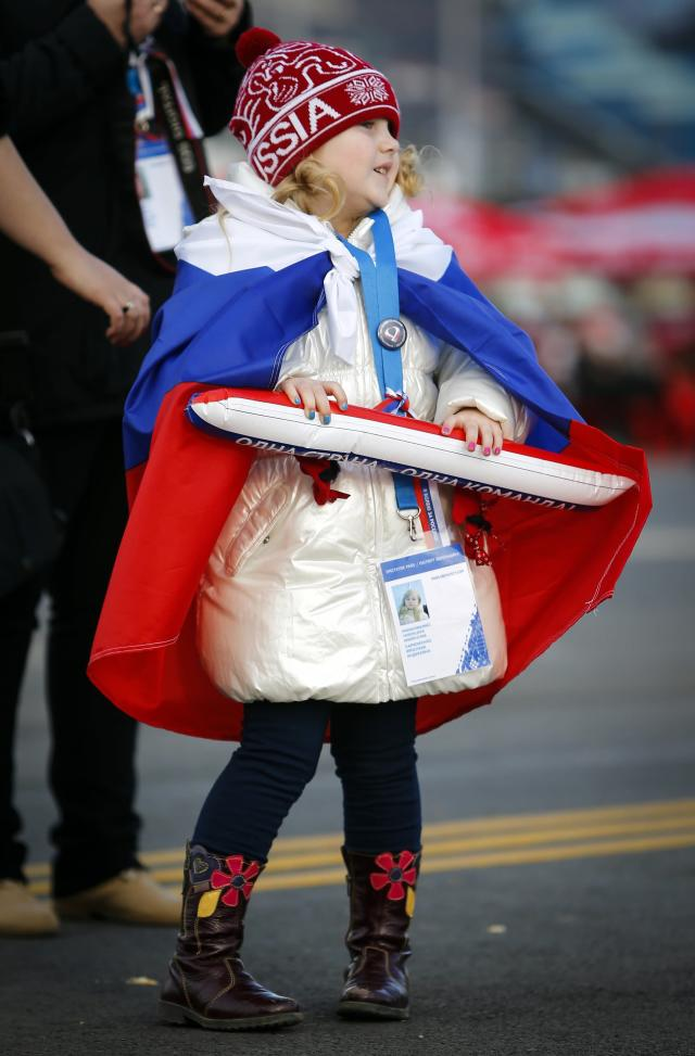 A girl carries one half of a clapper at the Olympic Park during the Sochi 2014 Winter Olympics Games February 9, 2014. REUTERS/Shamil Zhumatov (RUSSIA - Tags: SPORT OLYMPICS)