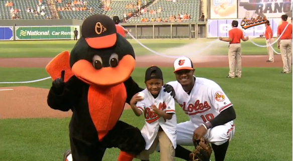 Zion poses with Adam Jones and the Orioles mascot after throwing the first pitch at the Orioles-Rangers game on August 2, 2016.