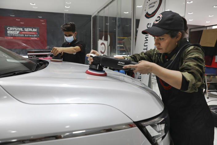 Iranian car detailer Maryam Roohani, right, and her brother Reza polish a car at a detailing shop in Tehran, Iran, April 18, 2021. Maryam Roohani has battled skeptics and stereotypes to live out her dream of working as a professional detailer. The auto industry remains male-dominated around the world, let alone in the tradition-bound Islamic Republic. (AP Photo/Vahid Salemi)
