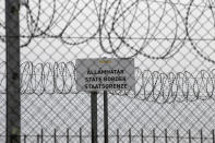 """FILE - In this Monday, April 8, 2019 file photo, a sign reading: """"State Border"""" is attached to a fence at Hungary's border with Serbia near the village Asotthalom, Hungary. When Hungary and Poland joined the European Union in 2004, after decades of Communist domination, they thirsted for Western democratic standards and prosperity yet, 17 years later, as the EU ramps up efforts to rein in democratic backsliding in both countries, some of the governing right-wing populists in Hungary and Poland are comparing the bloc to their former Soviet oppressors — and flirting with the prospect of exiting the bloc. (AP Photo/Darko Vojinovic, File)"""