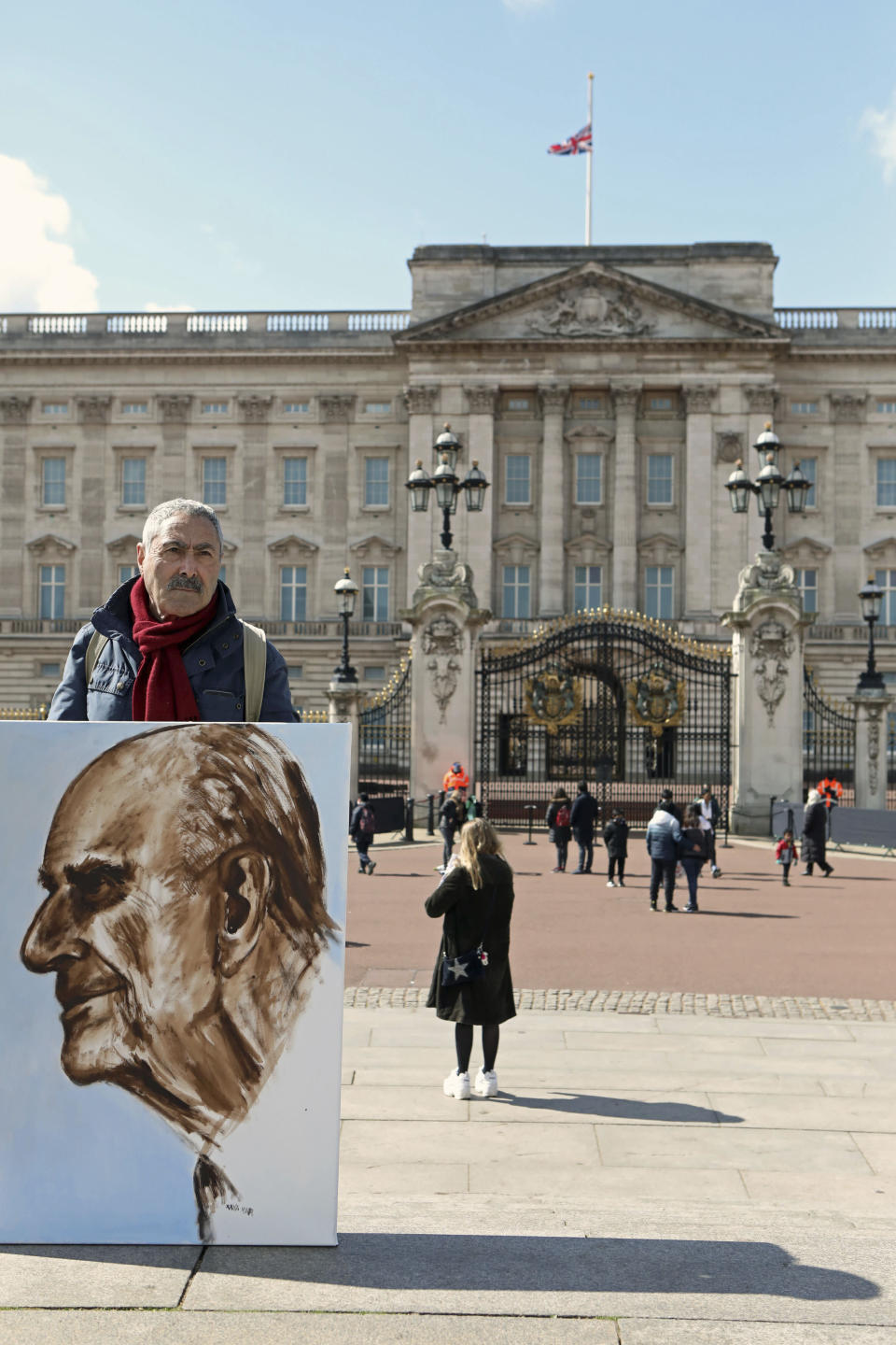 Artist Kaya Mar holds a portrait he has painted of the Duke of Edinburgh outside Buckingham Palace, London, Monday, April 12, 2021. Britain's Prince Philip, the irascible and tough-minded husband of Queen Elizabeth II who spent more than seven decades supporting his wife in a role that mostly defined his life, died on Friday. (Luciana Guerra/PA via AP)