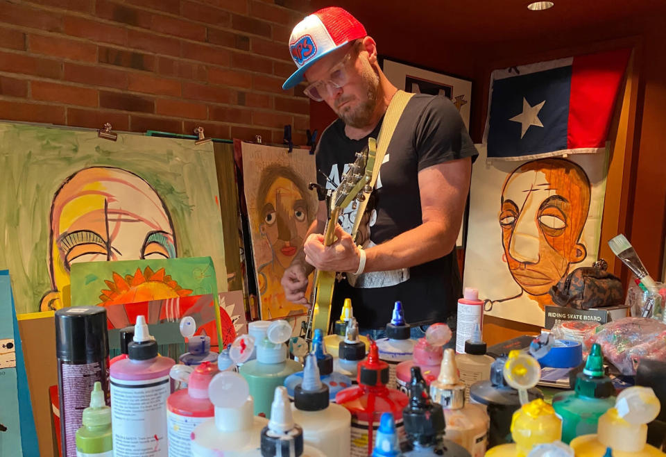 """Pearl Jam bassist and co-founder Jeff Ament appears in his home studio among his artwork which was used as cover art for his solo album """"I Should Be Outside."""" (Pandora Andre-Beatty via AP)"""