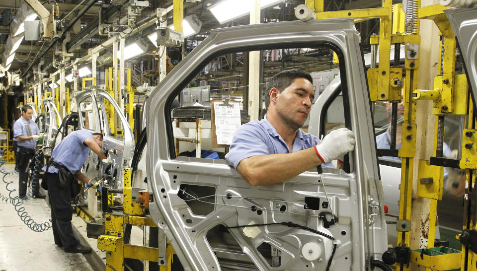 Employees work on the assembly line at the Renault plant in Sao Jose dos Pinhais August 2, 2012. President of the Brazilian branch for French automaker Renault SA Olivier Murguet said on Thursday that Renault SA plans to expand the capacity of its Brazilian motor plant by 25 percent by 2013 as part of a sales offensive in Latin America's largest economy.     REUTERS/Rodolfo Buhrer (BRAZIL - Tags: BUSINESS TRANSPORT)