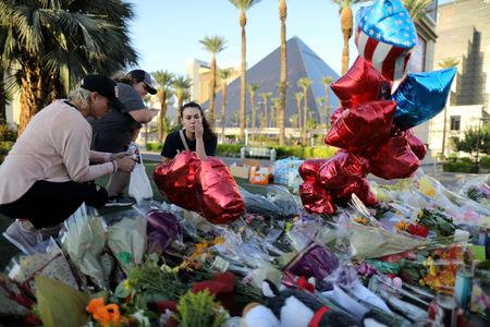FILE PHOTO: People leave flowers at a makeshift memorial on the Las Vegas Strip for victims of the Route 91 music festival mass shooting next to the Mandalay Bay Resort and Casino in Las Vegas