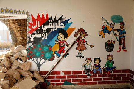 """A mural, that reads """"my way to my kindergarten"""", is seen in a kindergarten that was damaged during clashes between Libyan forces and Islamic State militants in Sirte, Libya, November 1, 2017. Picture taken November 1, 2017. REUTERS/Ahmed Jadallah"""