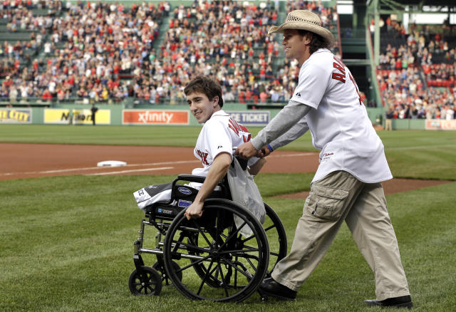 "FILE - Boston Marathon bombing survivor Jeff Bauman, left, is wheeled out by Carlos Arredondo, the man who helped save his life, to throw out the ceremonial first pitch at Fenway Park in a Tuesday, May 28, 2013 file photo, prior to a baseball game between the Boston Red Sox and the Philadelphia Phillies, in Boston. Bauman is working on a memoir with Grand Central Publishing to be titled ""Stronger,"" scheduled to come out in April. Grand Central announced Wednesday, Sept. 4, 2013 that the book would focus on Bauman's experiences during and after the bombings. (AP Photo/Elise Amendola, File)"