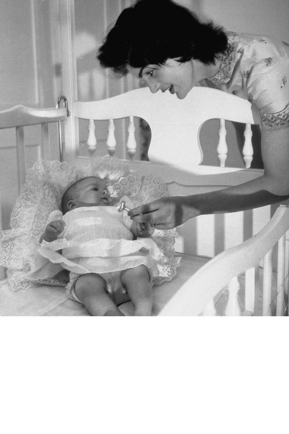 <p>Consider it mom and baby style done right. Here, Jackie is pictured with her new daughter Caroline Kennedy in 1958 in a silk printed dress.</p>