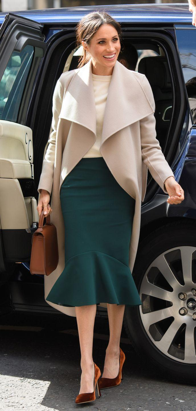 """<p>For a visit to northern Ireland, Markle teamed a <a class=""""link rapid-noclick-resp"""" href=""""https://shop.nordstrom.com/s/mackage-double-face-front-drape-wool-coat/4870274"""" rel=""""nofollow noopener"""" target=""""_blank"""" data-ylk=""""slk:Double-Face Front Drape Wool Coat by Mackage"""">Double-Face Front Drape Wool Coat by Mackage</a>, with a green skirt by <a class=""""link rapid-noclick-resp"""" href=""""https://gretaconstantine.com/index.html"""" rel=""""nofollow noopener"""" target=""""_blank"""" data-ylk=""""slk:Greta Constantine"""">Greta Constantine</a>. She layered up in a cream cashmere sweater by Victoria Beckham (similar <a class=""""link rapid-noclick-resp"""" href=""""https://www.harrods.com/en-gb/victoria-beckham/cashmere-sweater-p000000000005873768?ranMID=36666&ranEAID=Hy3bqNL2jtQ&ranSiteID=Hy3bqNL2jtQ-ZhVAkd0bZbQRUrCa1ccmEA&cid=LS&siteID=Hy3bqNL2jtQ-ZhVAkd0bZbQRUrCa1ccmEA"""" rel=""""nofollow noopener"""" target=""""_blank"""" data-ylk=""""slk:here"""">here</a>) and carried a <a class=""""link rapid-noclick-resp"""" href=""""https://www.charlottelizabeth.com/collections/the-bloomsburys"""" rel=""""nofollow noopener"""" target=""""_blank"""" data-ylk=""""slk:Bloomsbury's bag"""">Bloomsbury's bag</a> from young British designer Charlotte Elizabeth - currently sold out but Ice Coffee colour available <a href=""""https://www.charlottelizabeth.com/collections/the-bloomsburys/products/the-iced-latte-bloomsbury"""" rel=""""nofollow noopener"""" target=""""_blank"""" data-ylk=""""slk:here"""" class=""""link rapid-noclick-resp"""">here</a> - and wore Manolo Blahnik suede pumps (similar available <a class=""""link rapid-noclick-resp"""" href=""""https://www.harrods.com/en-gb/manolo-blahnik/suede-bb-pumps-105-p000000000003487182?bcid=1468336489856"""" rel=""""nofollow noopener"""" target=""""_blank"""" data-ylk=""""slk:here"""">here</a>).</p>"""