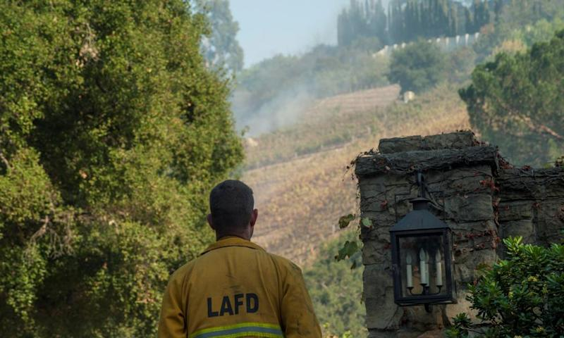 A firefighter stands outside a vineyard owned by Rupert Murdoch. The estate has been evacuated, though the house appeared undamaged.