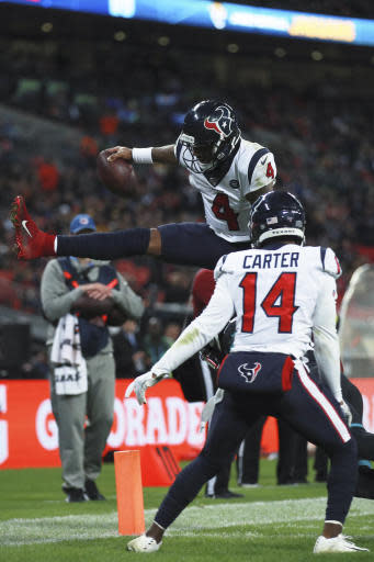 Houston Texans quarterback Deshaun Watson (4) leaps in the air against the Jacksonville Jaguars during the second half of an NFL football game at Wembley Stadium, Sunday, Nov. 3, 2019, in London. (AP Photo/Ian Walton)