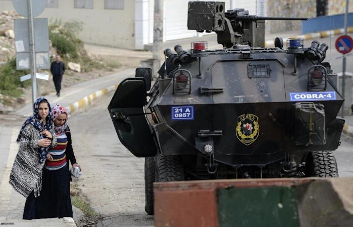 People walk by a military vehicle in a street of Silvan, Turkey during a curfew following clashes between Turkish forces and Kurdish militants on November 10, 2015 (AFP Photo/Ilyas Akengin)