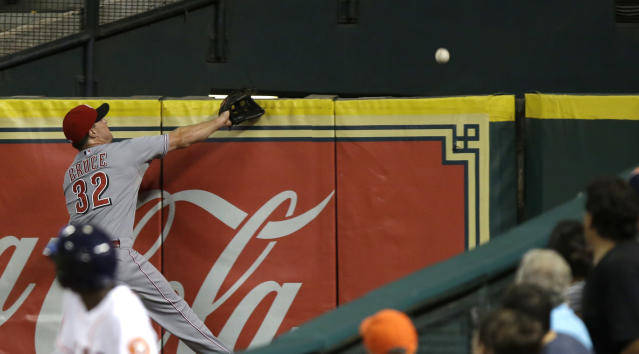 A ball boy and fans turn to watch Cincinnati Reds right fielder Jay Bruce's (32) futile attempt to catch a home run by Houston Astros' Brandon Barnes in the third inning of a baseball game Wednesday, Sept. 18, 2013, in Houston. (AP Photo/Pat Sullivan)