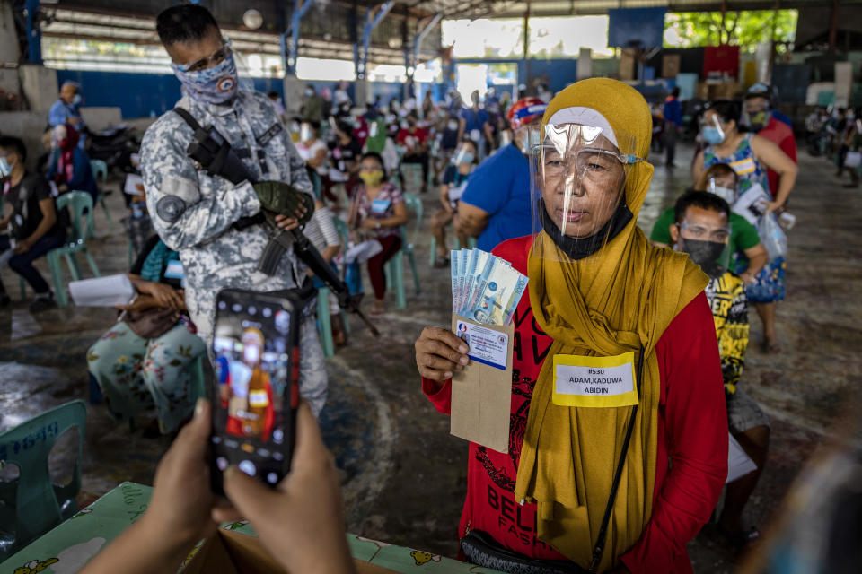 A social worker takes a picture of a resident receiving cash aid on April 7,2021 in Manila, Philippines. Each resident is entitled to 1,000 pesos ($20), with a limit of 4,000 pesos ($80) per household. Some 24 million people in Manila and nearby provinces remain under strict lockdown, the longest in the world, as the worst COVID-19 surge in Southeast Asia continues to hammer the country's healthcare system. (Photo by Ezra Acayan/Getty Images)