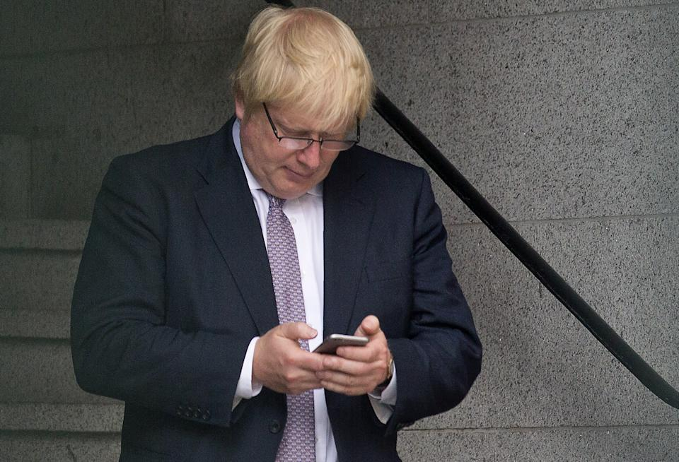 Former London mayor and Brexit campaigner Boris Johnson uses a mobile phone as he walks through buildings inside the Houses of Parliament and Portcullis House in central London on June 27, 2016. - Top Brexit campaigner Boris Johnson sought Monday to build bridges with Europe and with defeated Britons who voted to remain in the EU in last week's historic referendum. London stocks sank more than 0.8 percent in opening deals on Monday, despite attempts by finance minister George Osborne to calm jitters after last week's shock Brexit vote. (Photo by JUSTIN TALLIS / AFP) (Photo by JUSTIN TALLIS/AFP via Getty Images)