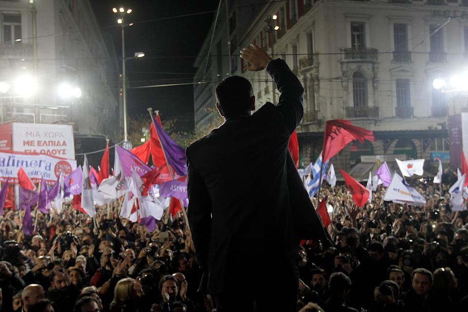 Alexis Tsipras, leader of Greece's Syriza left-wing main opposition party waves to his supporters as he arrives for a pre-election speech at Omonia Square in Athens Thursday, Jan. 22, 2015. (AP Photo/Orestis Panagiotou, Pool)