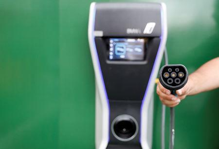 FILE PHOTO: Man holds an electric car charger in a car park at a McDonald's restaurant in Sao Paulo