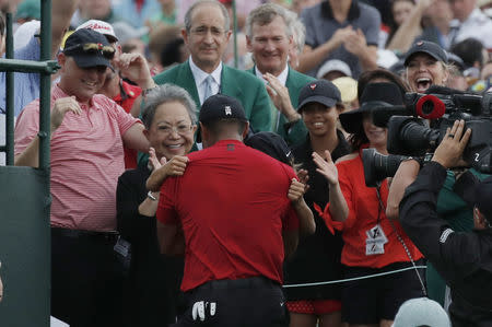 Golf - Masters - Augusta National Golf Club - Augusta, Georgia, U.S. - April 14, 2019 - Tiger Woods of the U.S. Tiger Woods embraces his son Charlie Axel as his mother Kultida Woods (L), daughter Sam Alexis and girlfriend Erica Herman (R) look on after he won the 2019 Masters. REUTERS/Mike Segar
