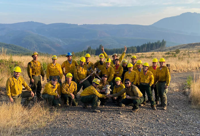 The Oregon Air National Guard pose for a group shot with Baby Yoda on Sept. 20, 2020 while fighting the Holiday Farm Fire in Blue River, Oregon. (Courtesy of Jaebyn Drake via AP) (Jaebyn Drake / AP)