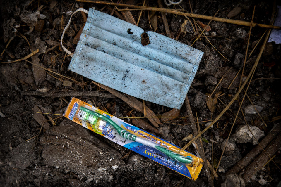 A face mask and an unused toothbrush of a deceased COVID-19 victim lie in a cremation ground in Gauhati, India, Friday, July 2, 2021. The personal belongings of cremated COVID-19 victims lie strewn around the grounds of the Ulubari cremation ground in Gauhati, the biggest city in India's remote northeast. It's a fundamental change from the rites and traditions that surround death in the Hindu religion. And, perhaps, also reflects the grim fears grieving people shaken by the deaths of their loved ones — have of the virus in India, where more than 405,000 people have died. (AP Photo/Anupam Nath)