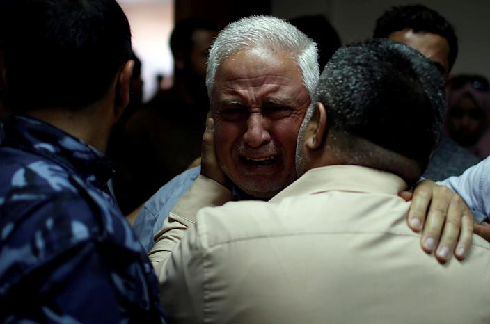 <p>A relative of Palestinian Ahmed al-Rantisi, who was killed during a protest at the Israel-Gaza border, is consoled at a hospital in the northern Gaza Strip, May 14, 2018. (Photo: Mohammed Salem/Reuters) </p>