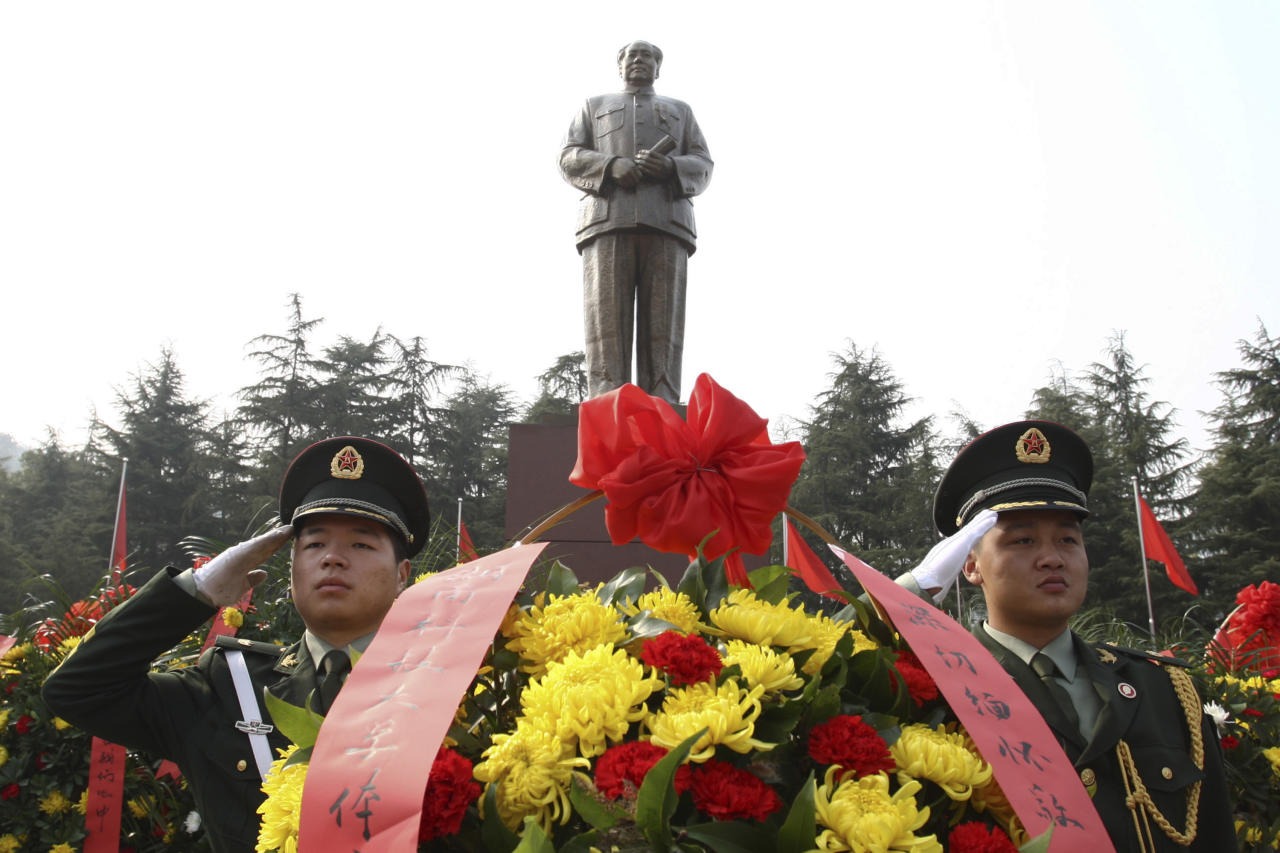 Security guards salute near wreaths in front of a statue of the late Communist leader Mao Zedong in Shaoshan, Mao's hometown, in southern China's Hunan province, Wednesday, Dec. 25, 2013. China's leaders bowed three times before a statue of Mao on the 120th anniversary of his birth Thursday in carefully controlled celebrations that also sought to uphold the market-style reforms that came after his death. (AP Photo) CHINA OUT