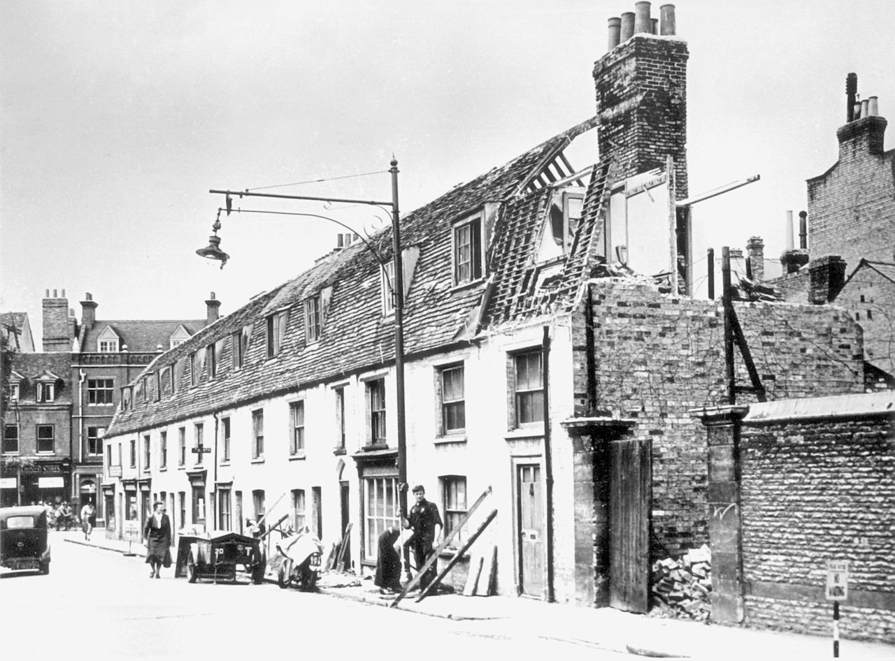 <p>Demolishing old terraced housing in Emmanuel Street, Cambridge, while a shop remains open at the other end (mediadrumworld/Caters) </p>