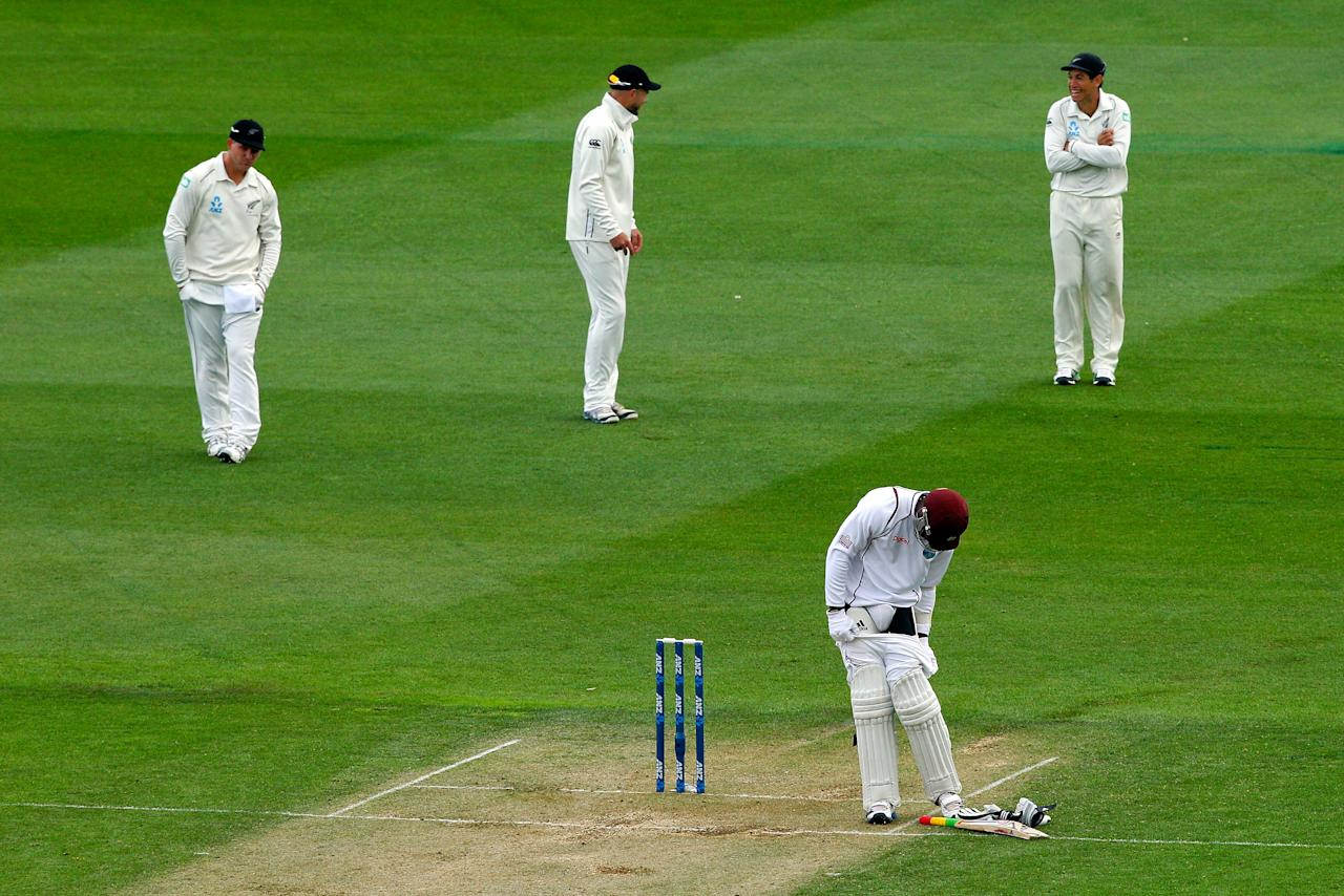 WELLINGTON, NEW ZEALAND - DECEMBER 12:  Kirk Edwards of the West Indies makes an adjustment to his gear while Corey Anderson, Peter Fulton and Ross Taylor of New Zealand look on during day two of the Second Test match between New Zealand and the West Indies at Basin Reserve on December 12, 2013 in Wellington, New Zealand.  (Photo by Hagen Hopkins/Getty Images)