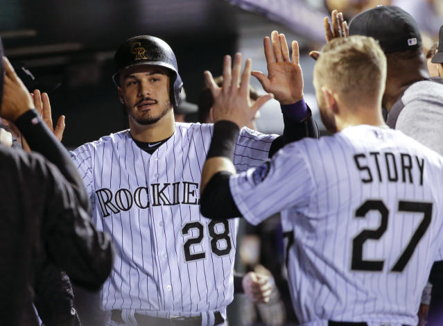 Colorado Rockies' Nolan Arenado (28) is congratulated by teammate Trevor Story (27) after scoring a run against the Philadelphia Phillies during the third inning of a baseball game on Monday, Sept. 24, 2018, in Denver. (AP Photo/Jack Dempsey)