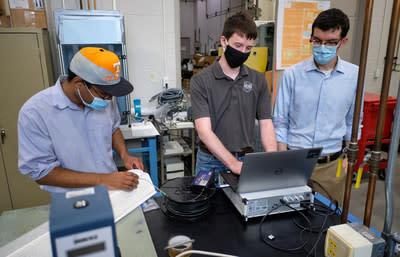 From left, Dr. Dayakar Penumadu's research group member Dr. Stephen Young, and graduate students Andrew Patchen and Joey Michaud are part of the University of Tennessee's team in Knoxville working to equip the fiber reinforced polymer bridge deck with high-density fiber optic and fiber Bragg grating sensors to monitor long-term durability.