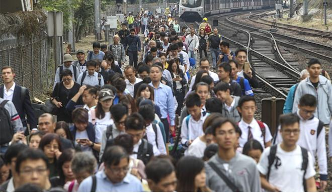 Commuters are forced to walk after trains are stopped by objects thrown on the tracks. Photo: Winson Wong