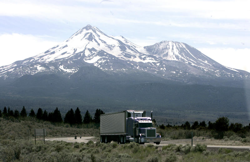 FILE - In this June 19, 2008 file photo, a truck drives past Mt. Shasta, near Weed, Calif. California regulators will hold a public hearing on Thursday, Dec. 12, 2019 about whether to require a certain percentage of truck sales to be zero emission vehicles. California has some of the worst air quality in the nation, largely driven by pollution from cars and trucks. (AP Photo/Rich Pedroncelli,file)