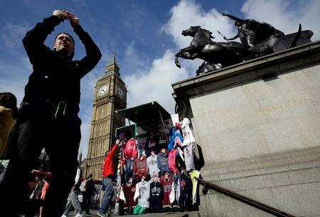 A man takes a picture near the Big Ben clock tower in London, Britain June 29, 2016. REUTERS/Kevin Coombs