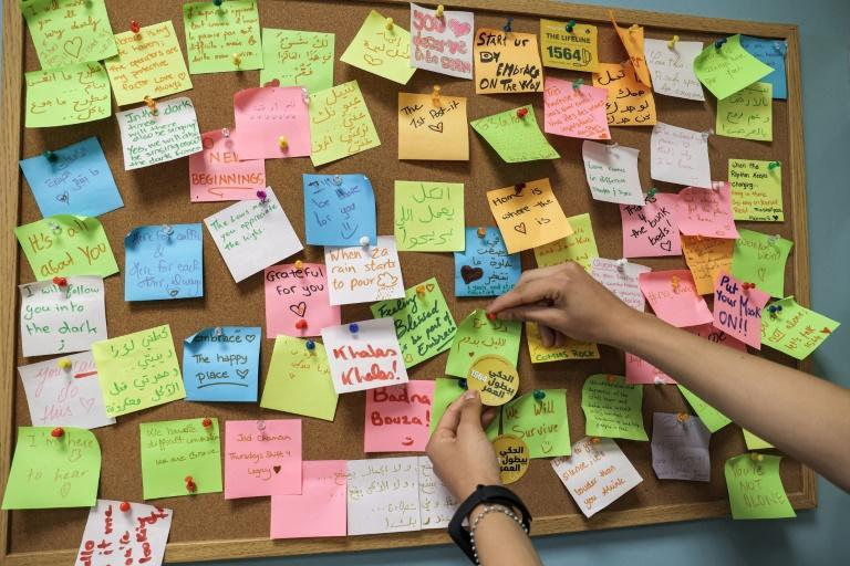 A woman places a note on a post-it board at the offices of Embrace, which says it receives around 1,100 calls a month (AFP/ANWAR AMRO)