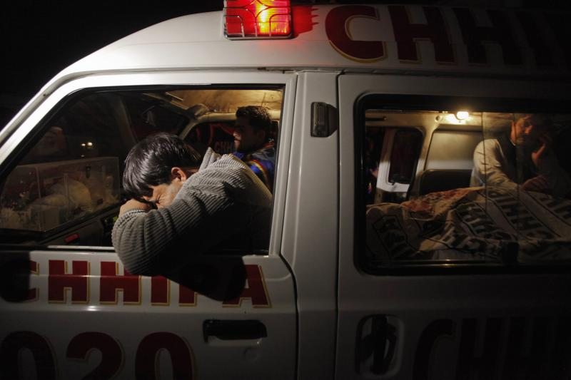 A relative mourns his family member, who was killed by unknown gunmen, next to his body in an ambulance, in Karachi