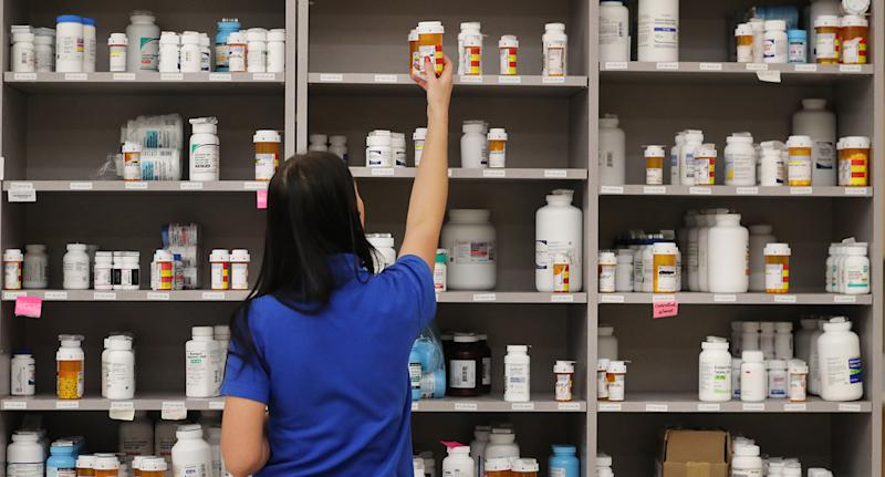 Pictured is a pharmacist getting medication off a shelf.