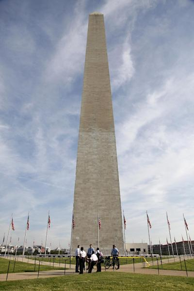 FILE -In this Aug. 24, 2011 file photo, Park Police officers and other security personnel gather at the base of the Washington Monument in Washington, as it remains closed after an earthquake. Repairs to the Washington Monument will require massive scaffolding to be built around the 555-foot obelisk and may keep it closed until 2014 after it was damaged by an earthquake last year. (AP Photo/Charles Dharapak, File)