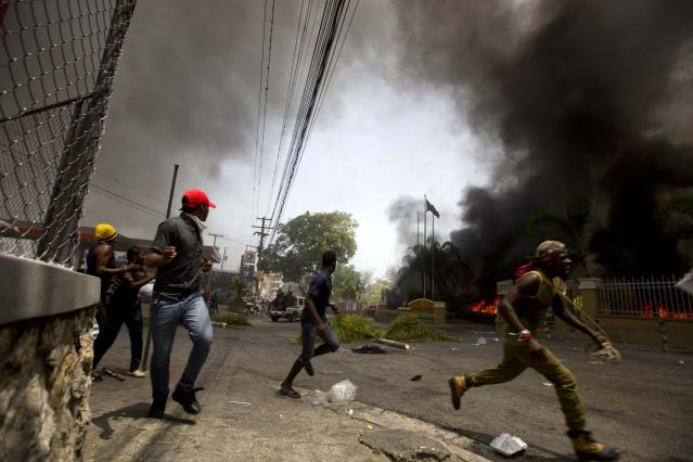 <p>People run away to protect themselves from police officers while cars burn in the garage of the Royal Oasis hotel during a protest over the cost of fuel in Port-au-Prince, Haiti, Saturday, July 7, 2018. (Photo: Dieu Nalio Chery/AP) </p>