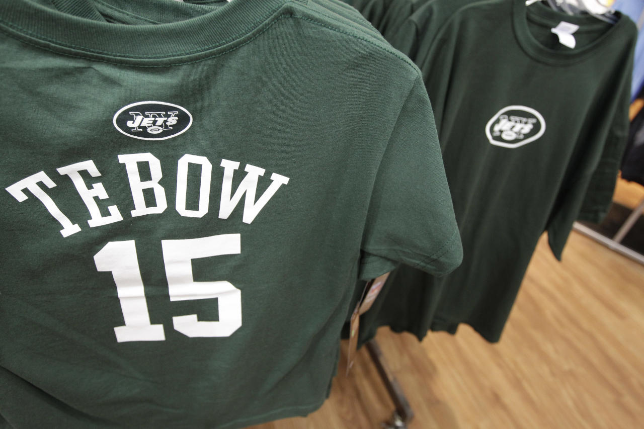 New York Jets shirts with the name and number of their new quarterback Tim Tebow hang on display at a Modell's store, Monday, March 26, 2012, in New York. At his introductory news conference Monday, the New York Jets backup quarterback, acquired from Denver last Wednesday, says he's grateful and excited to be with the team. (AP Photo/Mary Altaffer)