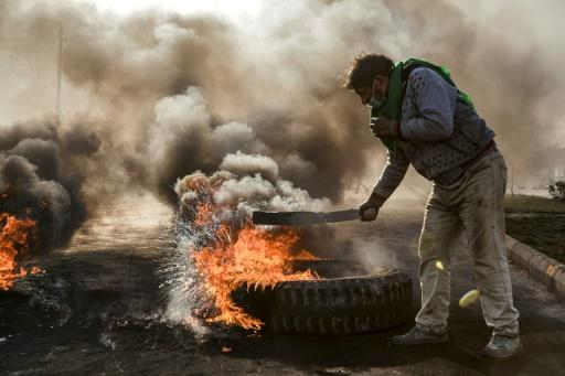 Anti-government protesters cut off a road with flaming tyres during a demonstration against Iraq's prime minister-designate Mohammad Allawi in the shrine city of Najaf, south of the capital