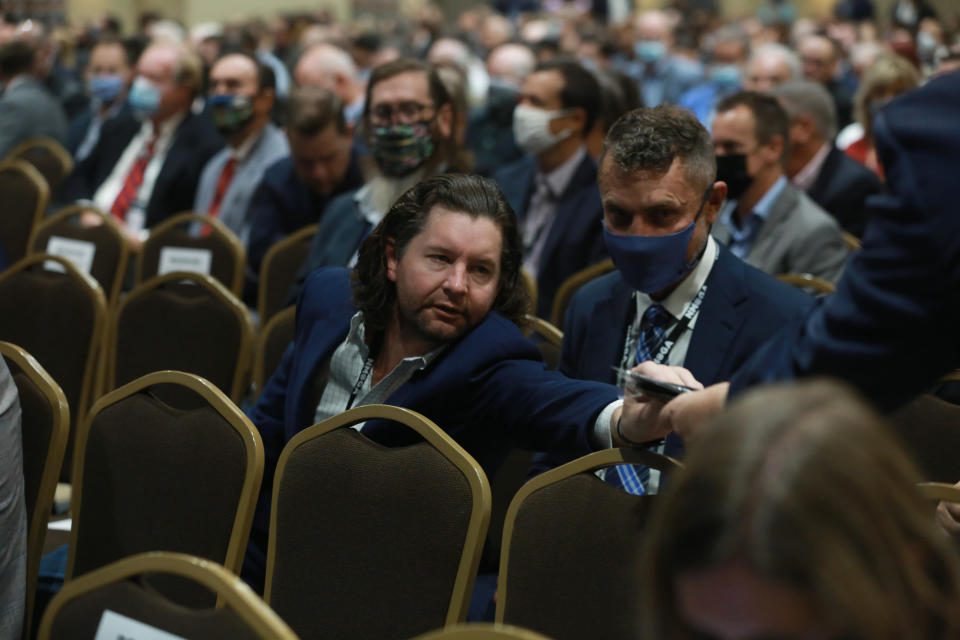 An attendee at the annual meeting of the New Mexico Oil And Gas Association reaches for a mask after the crowd was reminded to wear them by the state's governor, Monday, Oct. 4, 2021, in Santa Fe, New Mexico. Democratic Gov. Michelle Lujan Grisham addressed the crowd while moving to crack down on pollution from gas extraction. She's also trying to shield producers from a drilling moratorium by the Biden administration. New Mexico relies on oil and gas royalties for around one third of its budget. (AP Photo/Cedar Attanasio)