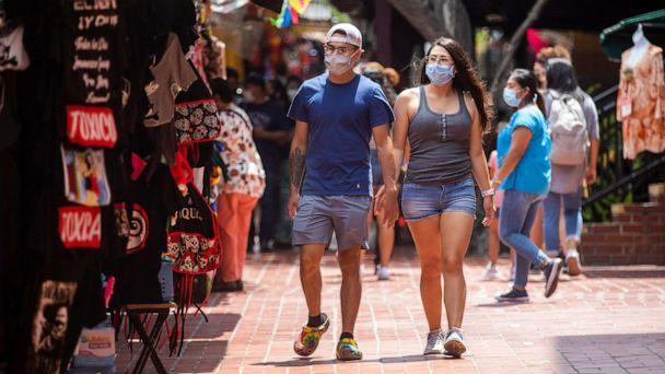 PHOTO: Pedestrians wearing Covid-19 masks walk through Olvera Street in Los Angeles, June 29, 2021. (Los Angeles Times via Getty Images, FILE)
