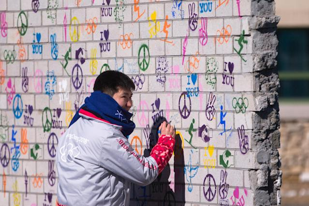 <p>A man writes on the Truce Mural unveiled in the Olympic Village at the 2018 Winter Olympic Games. (Sergei Bobylev\TASS via Getty Images) </p>