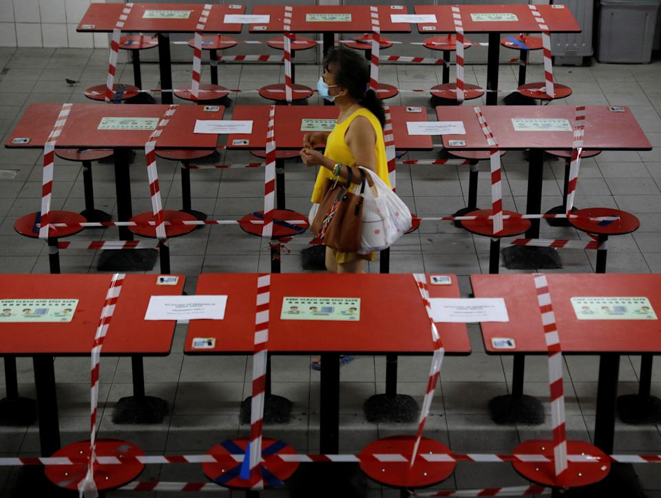 A woman walks between rows of taped up tables at a food centre as dining-in is restricted to curb the coronavirus disease (COVID-19) outbreak in Singapore May 17, 2021.   REUTERS/Edgar Su
