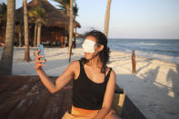 Mexico City resident Romina Montoya takes a playful selfie wearing a protective face mask over her eyes and nose, in Playa del Carmen, Quintana Roo state, Mexico, Wednesday, Jan. 6, 2021. Concern is spreading that the critical winter holiday tourism success could be fleeting because it came as COVID-19 infections in both Mexico and the United States were reaching new heights. (AP Photo/Emilio Espejel)