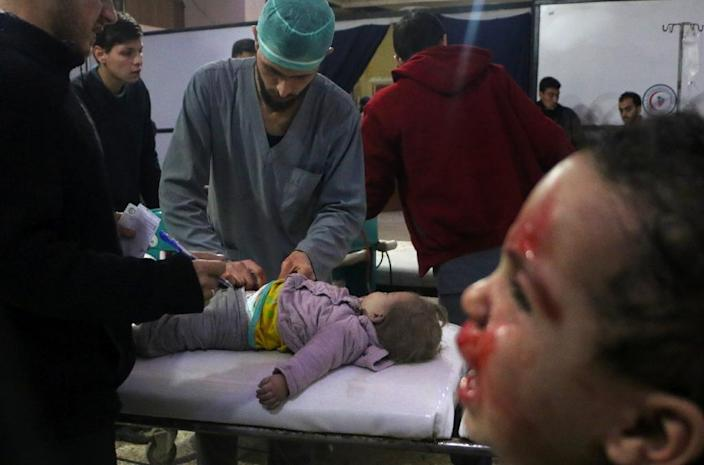 Syrian medics tend to a baby as a child cries next to them at a makeshift clinic following Syrian government bombardments in Douma, in besieged Eastern Ghouta (AFP Photo/Hamza AL-AJWEH)