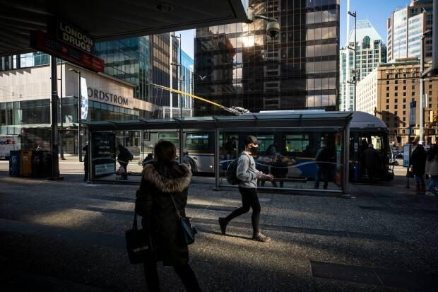 People are pictured walking along Granville Street in Vancouver in February. (Ben Nelms/CBC - image credit)