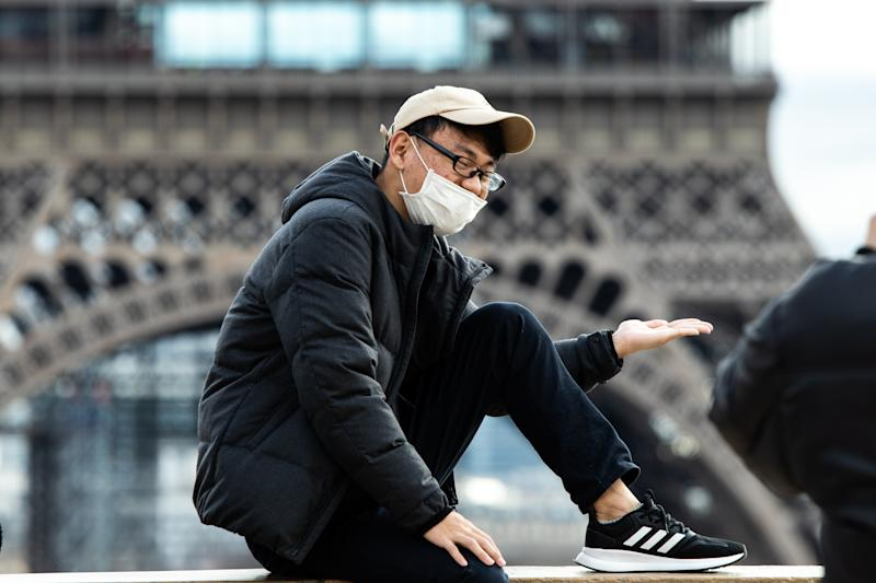 A Chinese tourist wears a face mask in front of the Eiffel Tower in Paris.