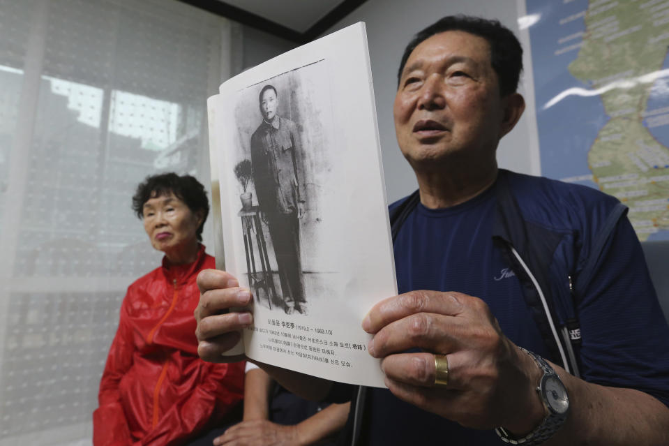 Lee Gwang-nam holding a photo of his father Lee Dol-mong speaks during an interview at a house of Shin Yun-sun, not in photo, in Seoul, South Korea Wednesday, July 29, 2020. The thousands of husbands and fathers who never returned from Sakhalin after eight decades is a largely forgotten legacy of Japan's brutal rule of the Korean Peninsula before the end of World War II. Lee, 76, and Shin, 75, are among about 400 aging relatives who hope to bring back the remains of the missing workers, seeking closure after years of emotional distress and economic hardship that affected many of the broken families.(AP Photo/Ahn Young-joon)