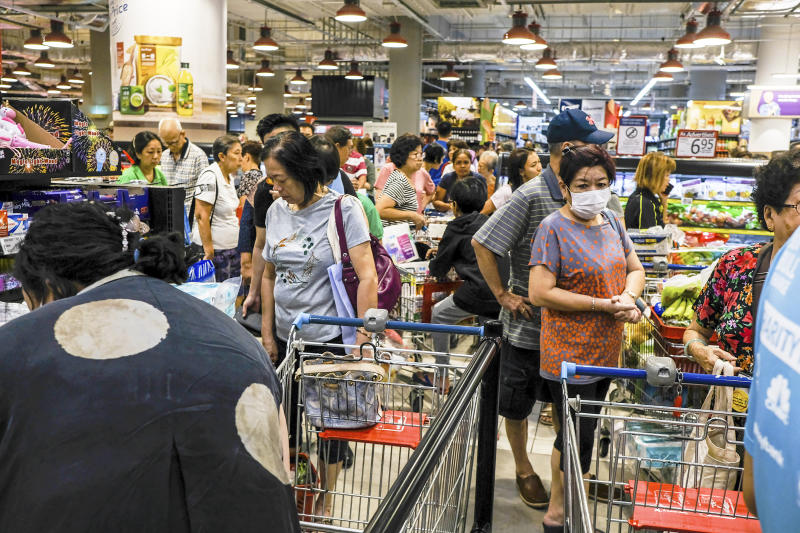 Shoppers wait in line to pay at a supermarket in Singapore, Tuesday, Mar. 17, 2020. Singaporeans were seen buying food supplies in supermarkets following neighboring Malaysia's announcement of a nationwide lockdown due to the coronavirus to begin Wednesday which could affect the flow of food supplies to the city state. (AP Photo/Ee Ming Toh)